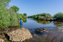 The teenager stands on top of a large stone boulder on the bank. Of the Sorraia River and looks at the river below. The river Sorraia in the summer - bright Stock Photos