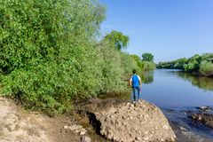 The teenager stands on top of a large stone boulder on the bank. Of the Sorraia River and looks at the river below. The river Sorraia in the summer - bright Royalty Free Stock Image