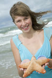 Teenager with starfish on the beach Royalty Free Stock Images