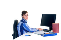 Teenager student doing homework. With computer and books on desk, white background Royalty Free Stock Photo