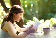 Teenager student girl reading book with tea cup royalty free stock photography
