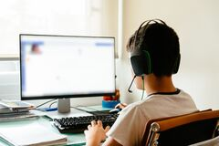 Teenager is studying at home attending online classes during the coronavirus COVID-19 pandemic quarantine