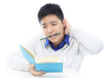 Teenager Studying. A teenager scratching his head while reading a book Royalty Free Stock Photos