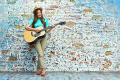 Teenager style portrait of young woman playing acoustic guitar. Against brick wall Royalty Free Stock Photography
