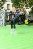 Teenager summersaulting on inflatable Stonehenge Royalty Free Stock Image