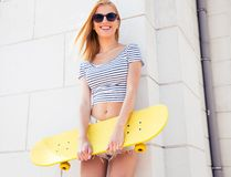 Teenager in sunglasses holding skateboard Royalty Free Stock Image