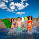 Teenager surfers group running beach splashing Royalty Free Stock Photos