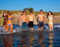 Teenager surfers group running beach splashing Royalty Free Stock Image