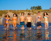 Teenager surfers group running beach splashing Stock Photos