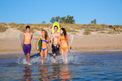Teenager surfers group running beach splashing Stock Image