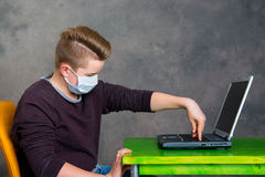 Teenager with surgical mask protect computer from virus Royalty Free Stock Photos