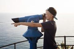 Teenager surveillances through telescope Royalty Free Stock Photography