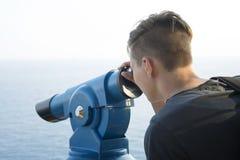 Teenager surveillances through telescope Stock Photo