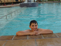 Teenager in swimming pool. Smiling teenager resting at side of swimming pool Royalty Free Stock Image