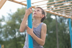 A teenager in a T-shirt climbs on a gymnastic pole royalty free stock image