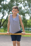 A teenager in a T-shirt is engaged in gymnastics on a horizontal bar Royalty Free Stock Photo