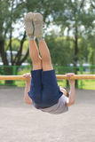 A teenager in a T-shirt is engaged in gymnastics on a horizontal bar Royalty Free Stock Photography