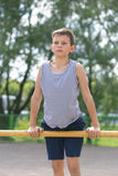 A teenager in a T-shirt is engaged in gymnastics on a horizontal bar Stock Photo