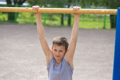 A teenager in a T-shirt is engaged in gymnastics on a horizontal bar Stock Photography