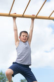 A teenager in a T-shirt is engaged in gymnastics on a horizontal bar Stock Photos