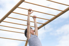 A teenager in a T-shirt is engaged in gymnastics on a horizontal bar Royalty Free Stock Images