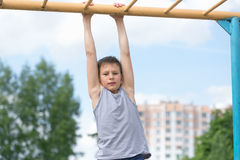 A teenager in a T-shirt is engaged in gymnastics on a horizontal bar Stock Image