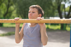 A teenager in a T-shirt is engaged in gymnastics on a horizontal bar Stock Images
