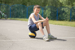 A teenager in a T-shirt is sitting on a ball resting Stock Photography