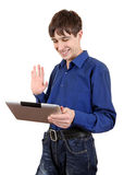 Teenager with Tablet Computer. Affable Teenager wave of the Hand to Tablet Computer Isolated on the White Background Stock Image