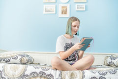 Teenager with tablet computer. Cute teenager girl with tablet computer at her bedroom Royalty Free Stock Photos