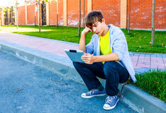 Teenager with Tablet Computer. Sad Teenager with Tablet Computer on the Street stock images