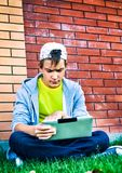 Teenager with a Tablet. Sad Teenager with Tablet Computer on the Street stock image
