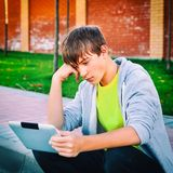 Teenager with a Tablet. Toned Photo of Sad Teenager with Tablet Computer on the Street stock photos
