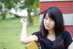 Teenager tailandese delle donne dell'Asia si rilassa sul parco Fotografia Stock Libera da Diritti
