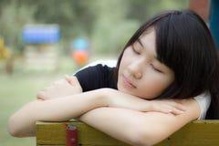 Teenager tailandese delle donne dell'Asia si rilassa sul parco Immagine Stock