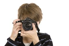Teenager Taking a Photo. A young guy using a DSLR pointed towards the camera, isolated on white Royalty Free Stock Image
