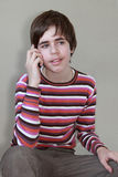 Teenager talking on the phone. On a gray background Royalty Free Stock Photos