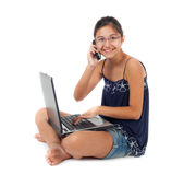 Teenager while talking on the phone with the laptop. Royalty Free Stock Photography