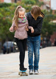 Teenager teaching sister skateboarding Royalty Free Stock Images