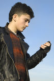 The Teenager with telephone. The Teenager with telephone on background sky Royalty Free Stock Photography