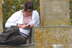 Teenager texting. Beautiful teenager texting using a mobile phone royalty free stock image