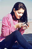 Teenager texting in the beach. Teenager sitting in the beach with her cellphone in hands and texting  in Mar del Plata, Argentina Royalty Free Stock Photography