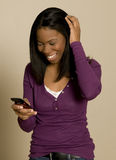 Teenager texting on cellphone. An African American teenager is using a cellphone royalty free stock image