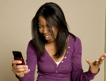 Teenager texting on cellphone. An African American teenager is using a cellphone stock photos