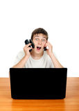 Teenager with Three Cellphones. Surprised Teenager with Three Mobile Phones at the Desk with Laptop Isolated on the White Royalty Free Stock Photography