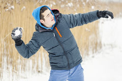 Teenager throw snowballs. In winter day stock image