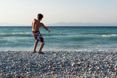 Teenager throwing stones into sea Royalty Free Stock Image