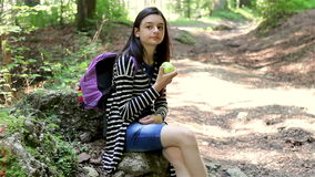 Teenager tourist girl eating apple in the forest stock video