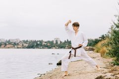 Boy in a white kimono with brown belt on a natural background. Intense karate exercise concept. Copy space. Royalty Free Stock Photo