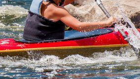 A teenager trains in the art of kayaking. Slalom on rough river rapids. The child is skillfully engaged in rafting. stock photos